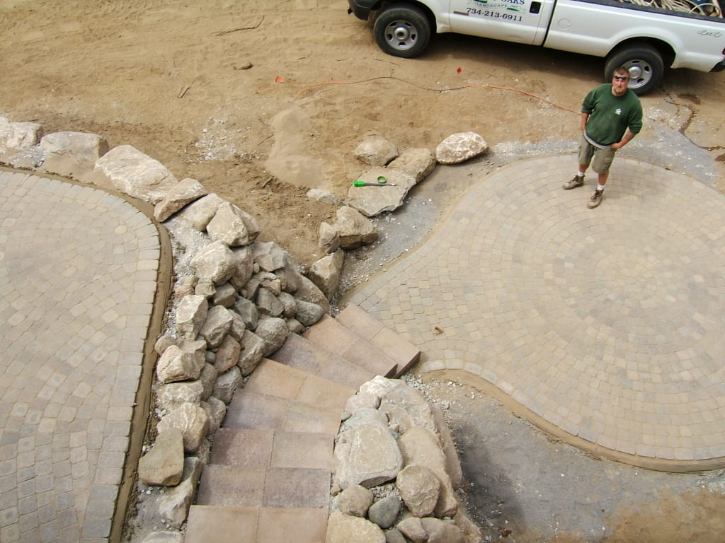 Twin Oaks employee standing on finished patio paver project