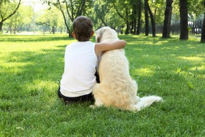 boy hugging his dog outside