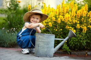 young boy with large watering can