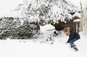 Father And Son Shoveling Snow Together In A Garden