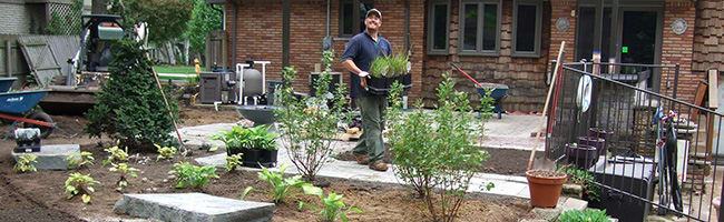 Twin Oaks worker carrying potted plants