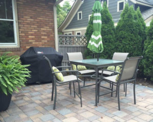 Brick paver patio with outdoor furniture and plants.