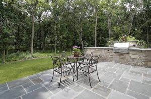 Beautiful paver patio with table and chairs and a built in grill.