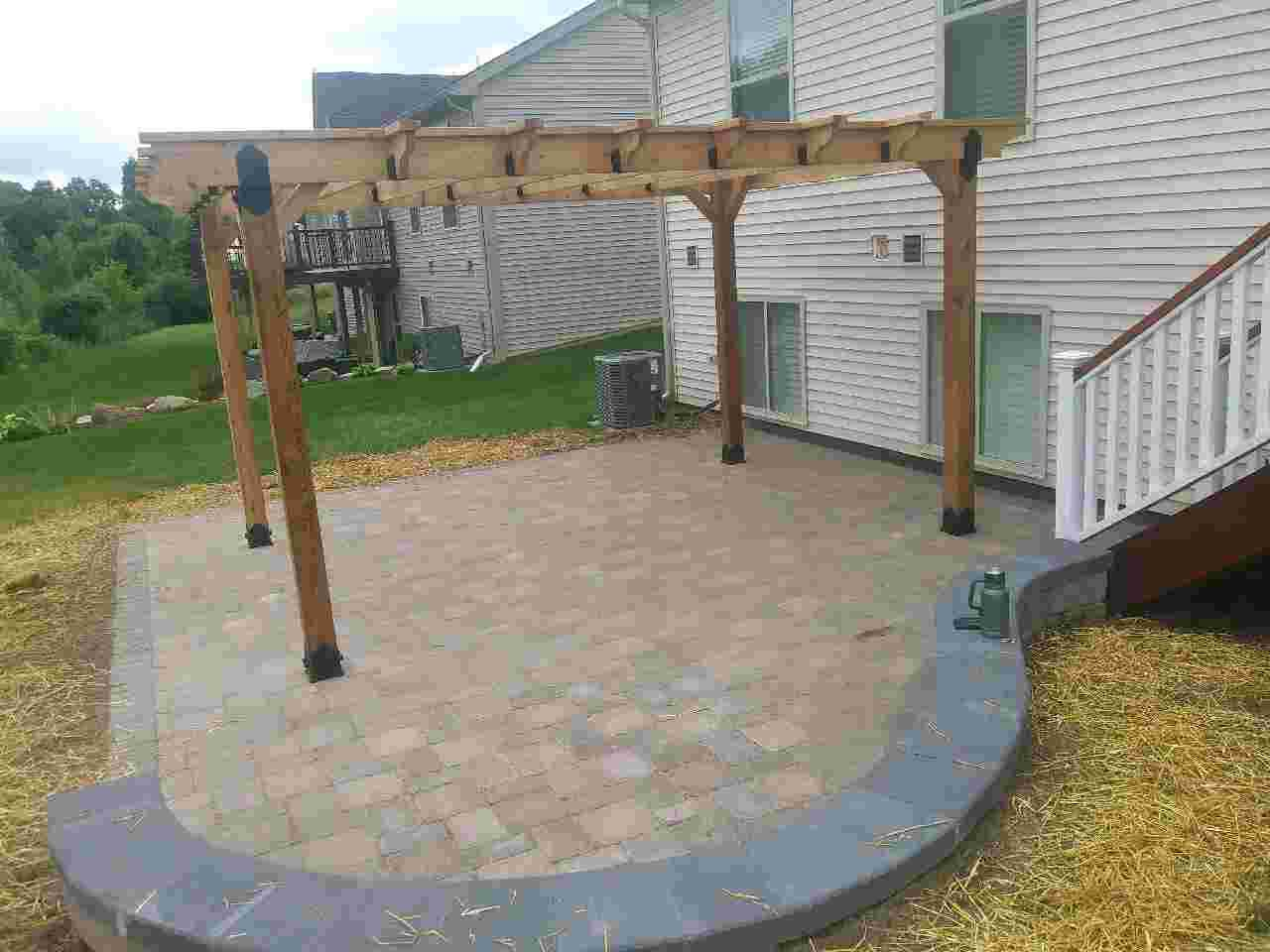 Paver patio, new pergola, and landscaping created by a professional landscape service.