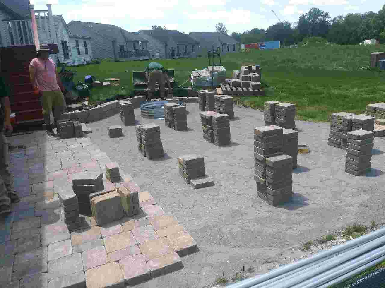 Installing paver patio and landscape in a backyard.