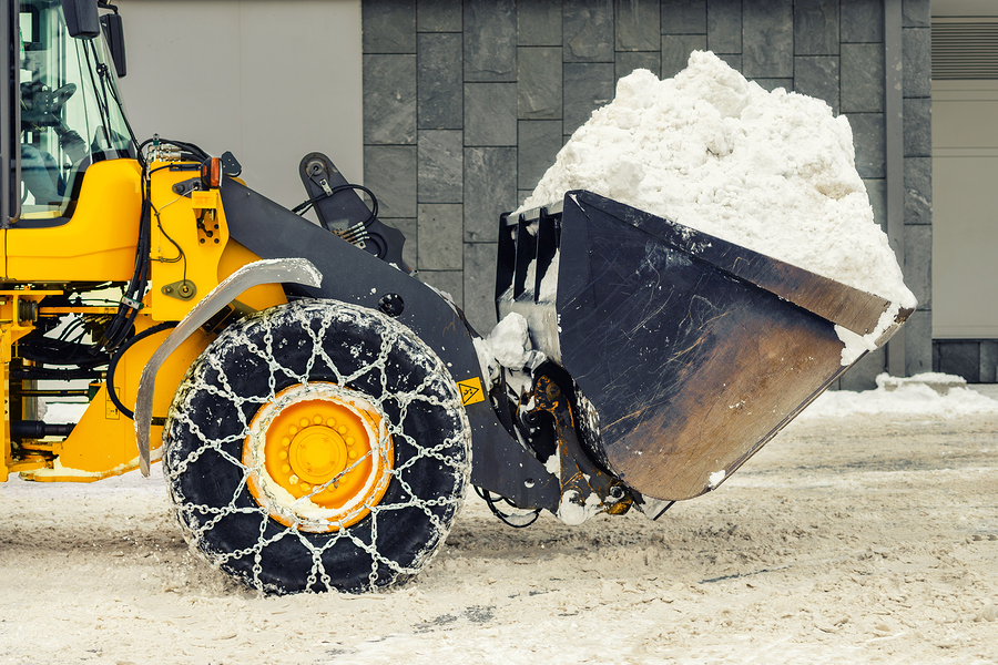 Commercial snow removal service cleaning up after a snow storm.