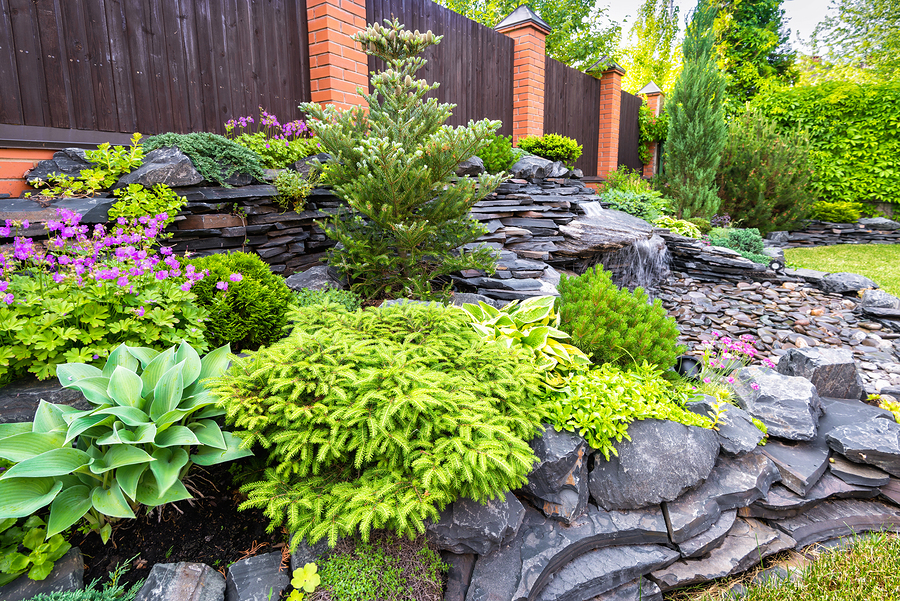 Beautiful residential landscape with flowers, shrubs, and stone.