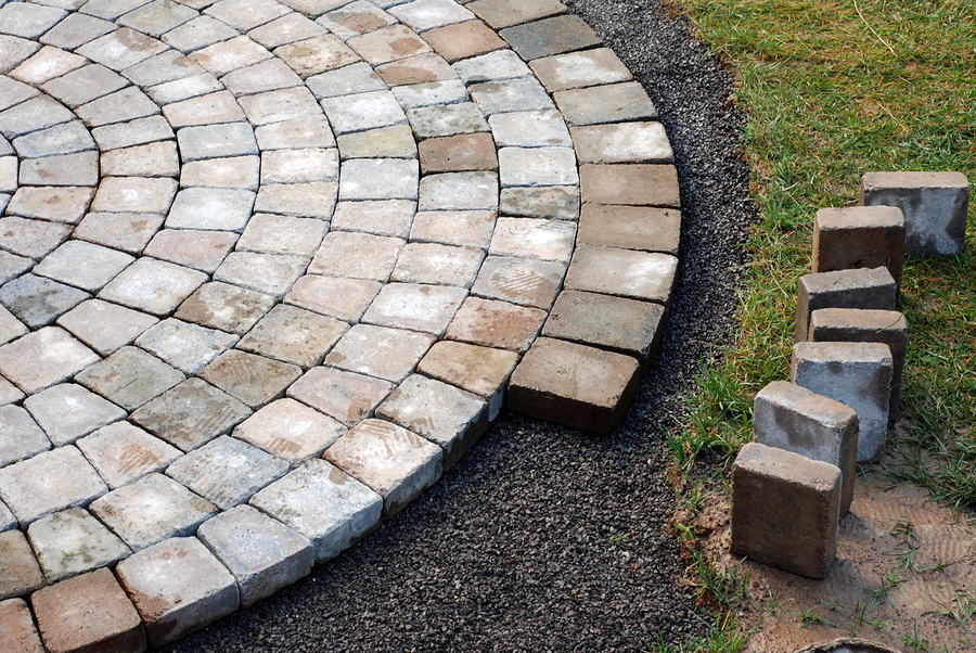 Paver patio being installed in a circular pattern.