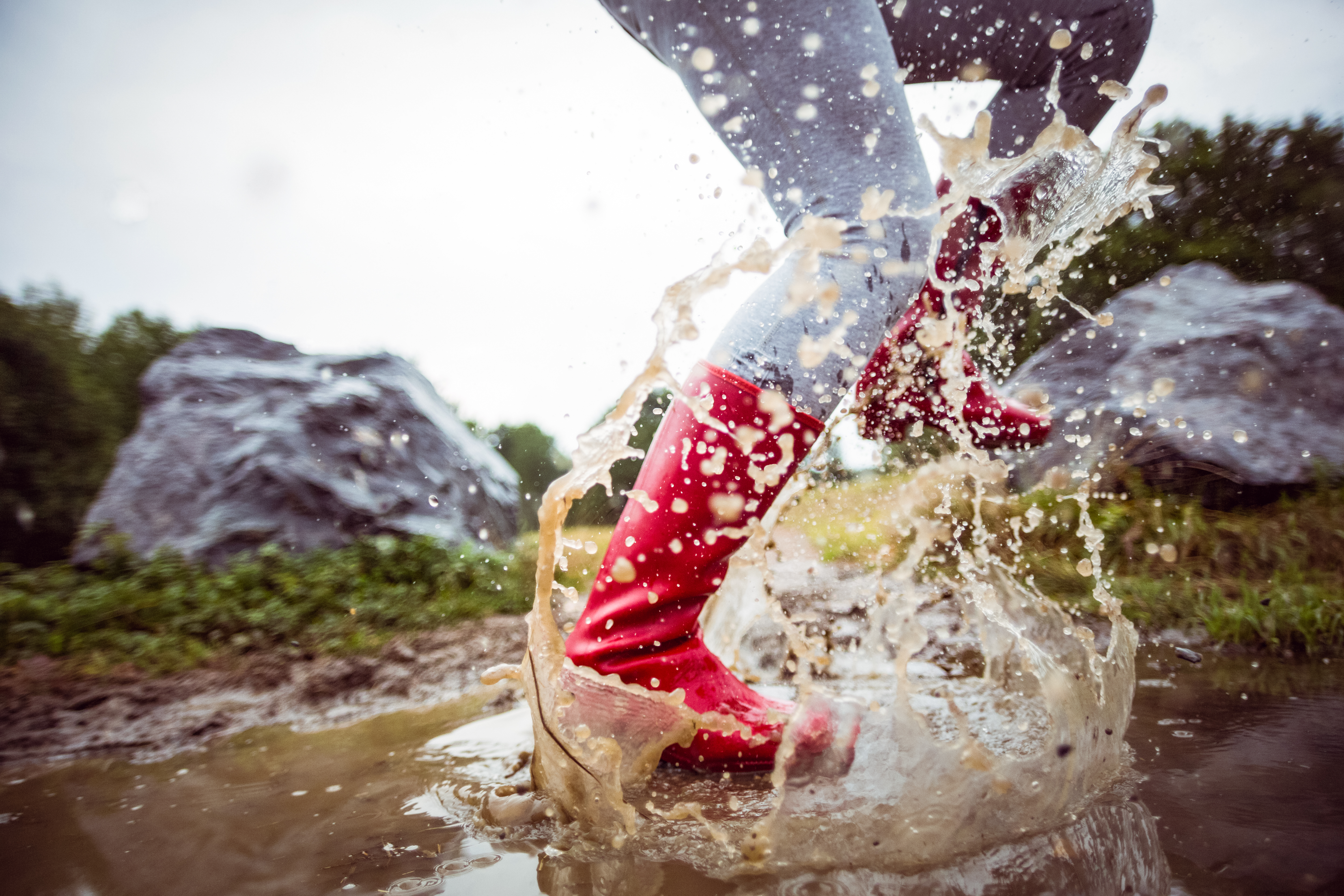 A woman wearing rain boots splashing through a puddle in the yard.