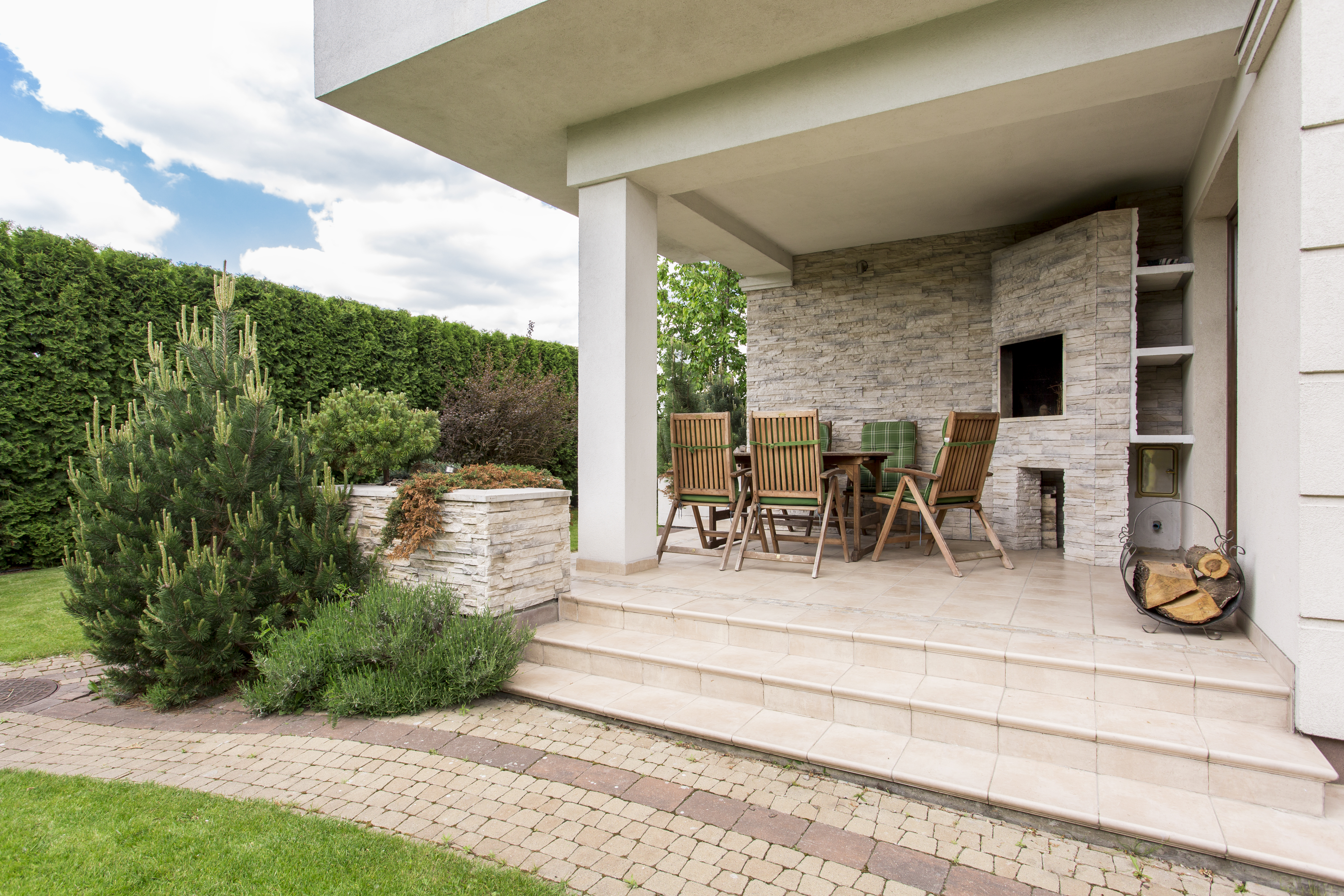 Modern house with cozy terrace and garden and beautiful paver walkway.