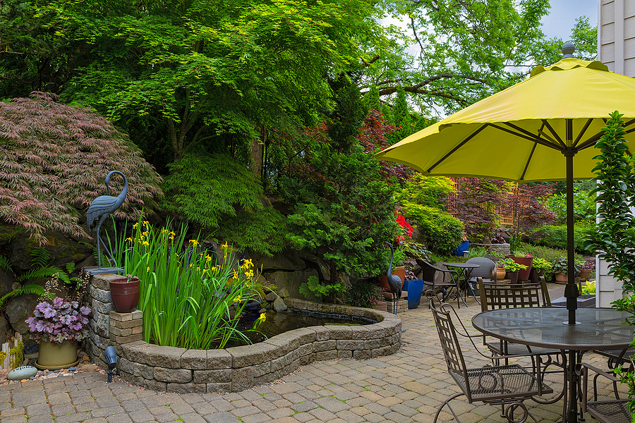 Home backyard hardscape and lush plants landscaping with garden furniture on paver brick patio.