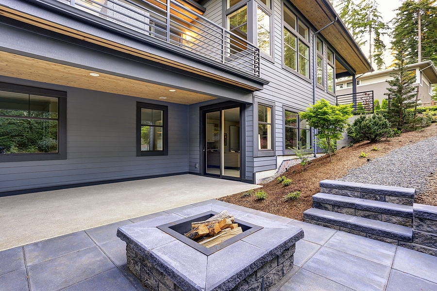 New modern home features a backyard with covered patio accented with a wood plank ceiling and a rectangular fire pit made of concrete and slate tiles.