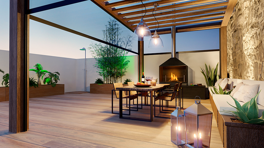 3D illustration of urban terrace at twilight with fire place and wooden table. Teak wood bioclimatic pergola and flooring.
