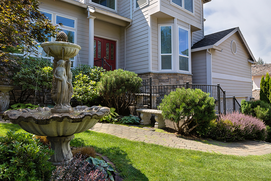 Residential single home in North America suburbs frontyard with manicured garden green lawn paver brick walkway bench and stone water fountain.